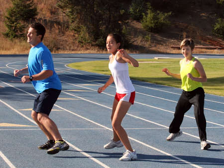 Mother, father and daughter exercising on a blue racetrack Stock Photo - 545064
