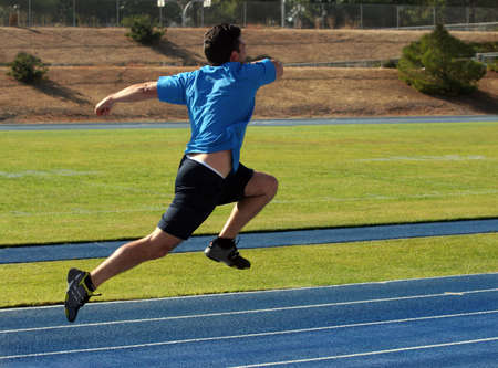 racetrack: Man running  on a blue racetrack Stock Photo