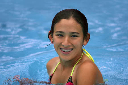 Happy teen girl with braces in the pool