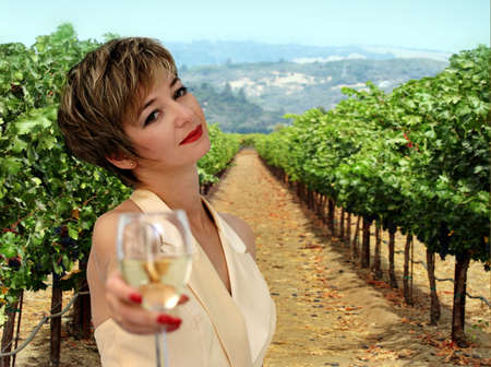 Beautiful woman offering a glass of white wine at vineyard