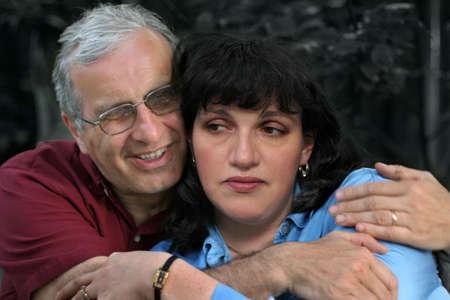 Mature man embracing his upset wife photo