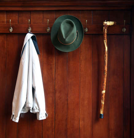 Stilleven od een houten kleding rack met een hoed, jas en een wandelstok
