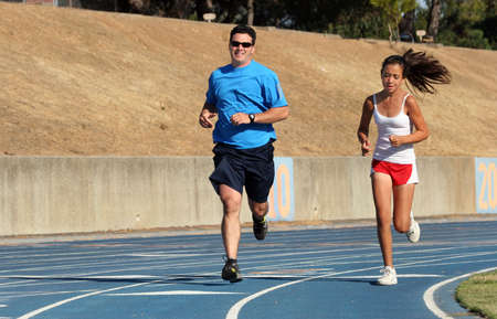 Father and daughter running on a blue racetrack Stock Photo