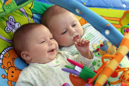 Two baby boys twin brothers playing together Imagens