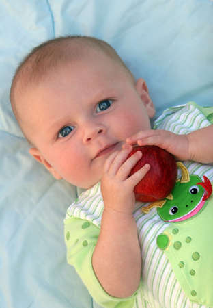 Cute happy 3 month old baby holding an apple photo