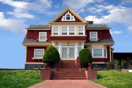 前面に芝生と美しい赤い家 写真素材
