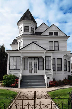 Beautiful Victorian white house with a lawn in front photo