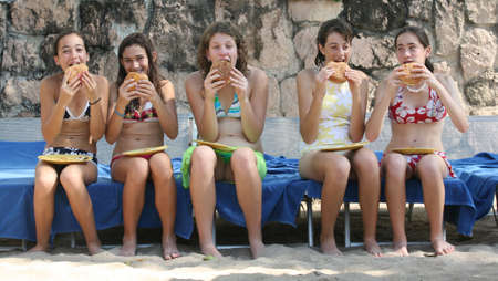 Five teenage girls eating humburgers on the beach Stock Photo