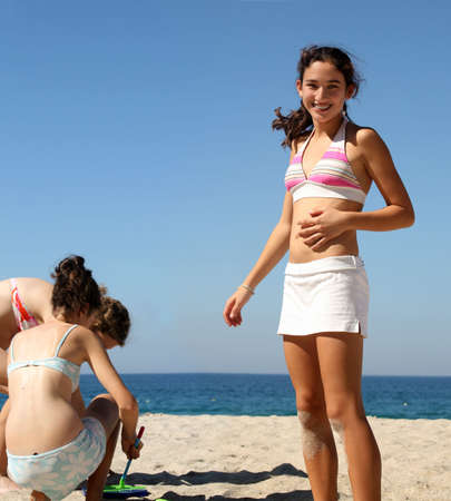 Three teen girls playing on the beach