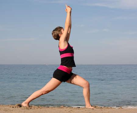 Woman doing yoga exercise on the beach