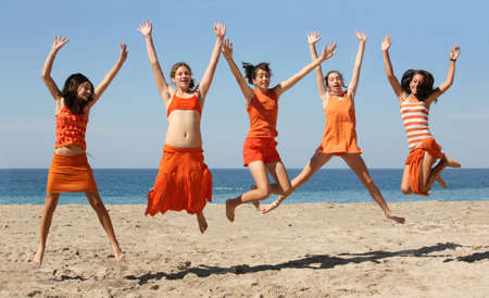 people celebrating: Five girls in orange clothes jumping on the beach Stock Photo
