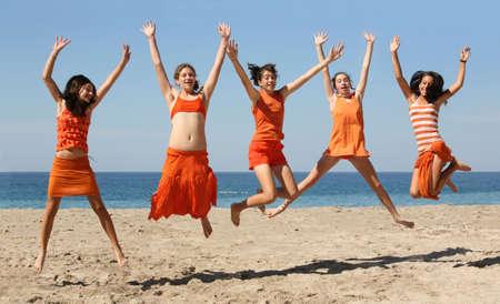 Vijf meisjes in oranje kleren springen op het strand