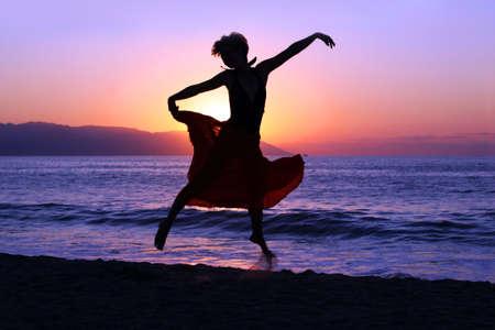 Drastisches Bild einer Frau, die durch den Ozean am Sonnenuntergang tanzt