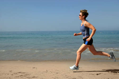 Young woman running alone on the beach Stock Photo