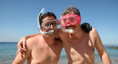 hombres gays: Dos hombres est�n a punto de ir buceando en el oc�ano  Foto de archivo