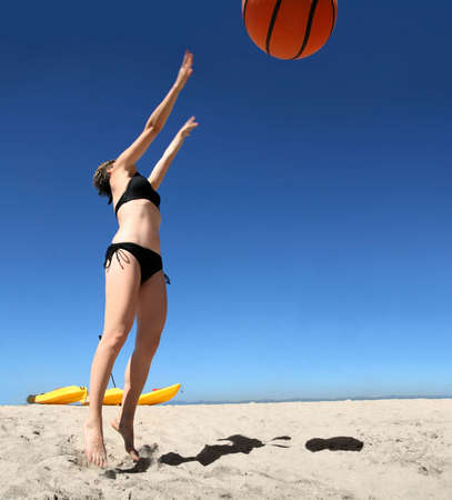 Girl playing with giant basketball on the beach