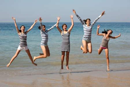 Vijf tienermeisjes springen op het strand Stockfoto