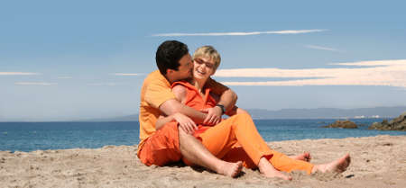 Happy couple in orange clothes on the beach Stock Photo - 642734