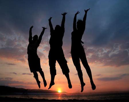 Drie mensen silhouetten springen op het strand