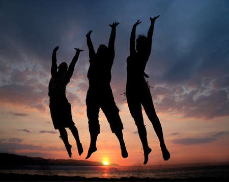 Three people silhouettes jumping on the beach photo