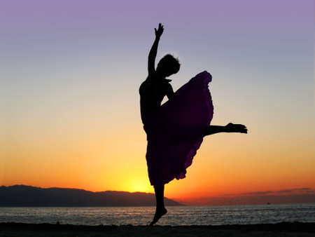 Dramatic image of a woman dancing by the ocean at sunset