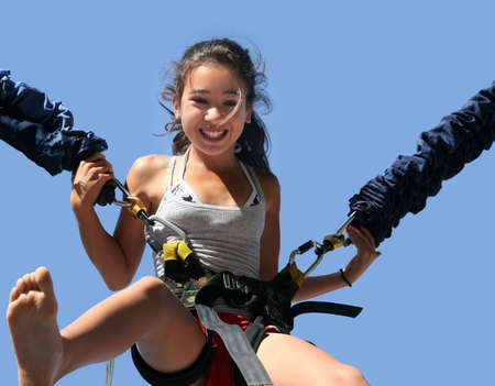 playground ride: Girl having a good time bungee jumping