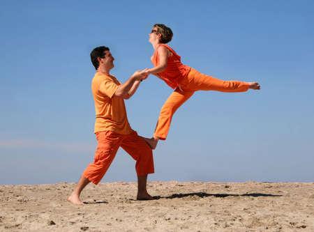Couple in orange clothes having fun on the beach
