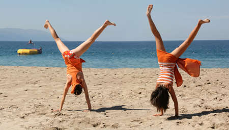 weekend activities: Two girls in orange clothes doing cartwheel on the beach Stock Photo