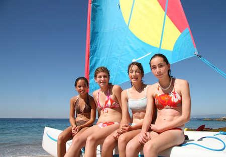 enfant maillot: Quatre adolescentes heureux assis sur un bateau