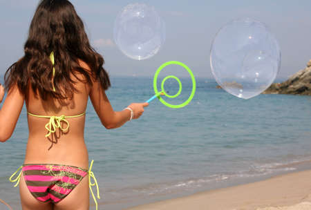 Teen girl playing with bubbles on the beach Standard-Bild