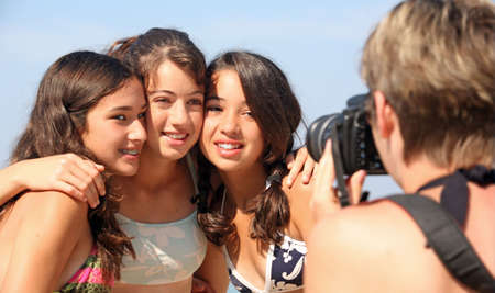Mother is taking pictures of three teenage girls Stock Photo