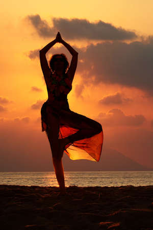 Woman doing yoga exercise on the beach at sunset