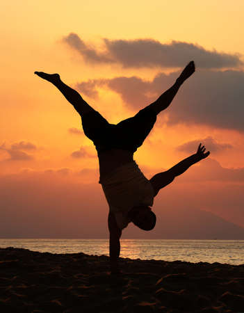 Young man is doing an amazing handstand at sunset Stock Photo