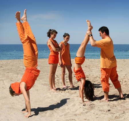 Family in orange clothes having fun on the beach Stock Photo