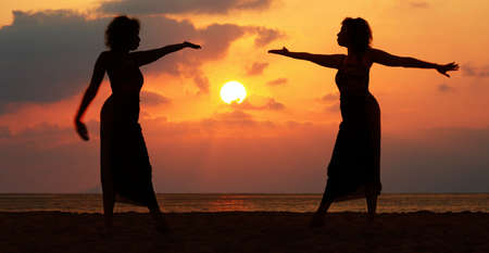 Dramatic image of two women by the ocean at sunset Stock Photo