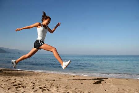 幸せな女の子、ビーチで単独で走っています。 写真素材
