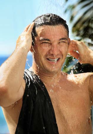 Knap gelukkig man neemt een douche buitenshuis