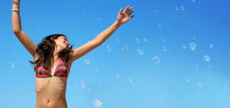 excitement: Happy girl playing with bubbles on the beach Stock Photo