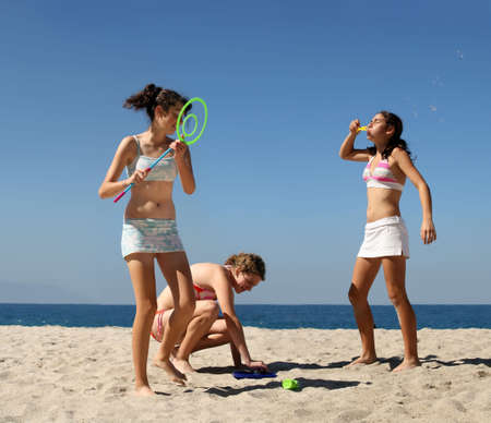 Three teen girls playing with bubbles on the beach Standard-Bild