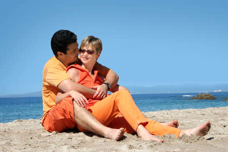 Happy couple in orange clothes on the beach