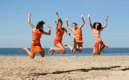 Vier meisjes in oranje kleren springen op het strand