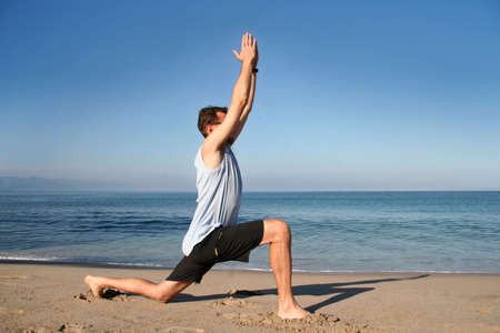 Man doing yoga exercise on the beach