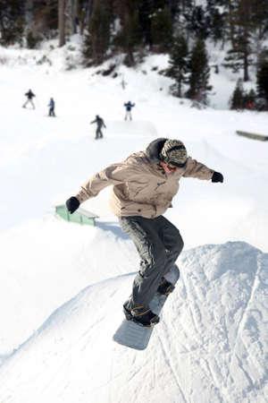 Teenager jumping high on a snowboard at the ski resort