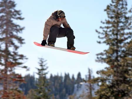 airborn: Teen girl jumping high on a snowboard