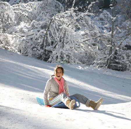 sledding: Teenage girl enjoying her sled ride Stock Photo