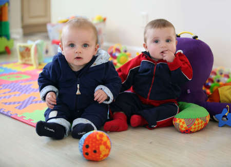 daycare: Cute baby brothers playing in the nursery Stock Photo