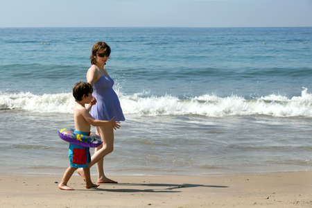 bikini couple: Pregnant mother and her son walking on the beach