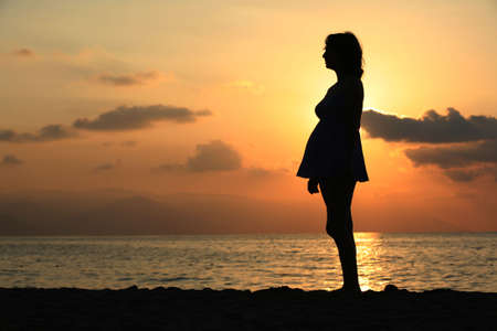 Pregnant woman standing on the beach at sunset photo