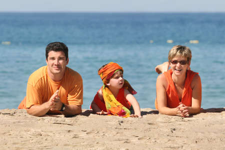 Family in orange clothes on the beach Stock Photo - 751141