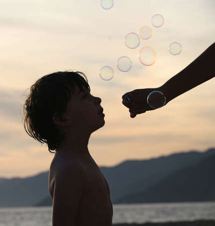 Boy playing with bubbles on the beach at sunset Stock Photo - 751142